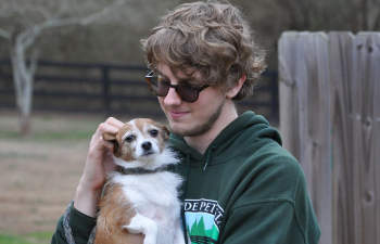 Countryside Pet Estateworker holding a petite dog in his arms