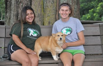 two Countryside Pet Estate workers sitting on bench with a corgi dog